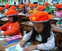 近視予防対策に台湾では、帽子にピンポン球を載せて授業を受ける